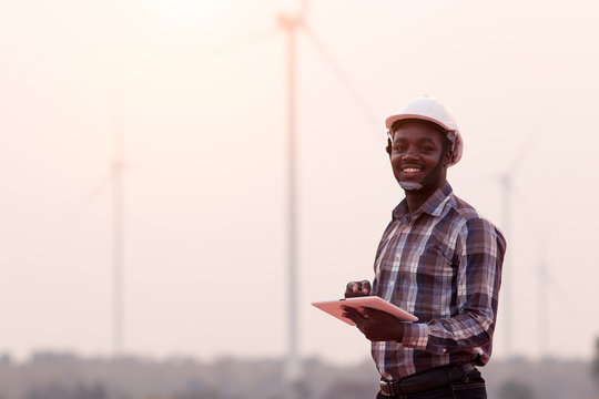 African engineer wearing white hard hat standing with digital tablet against wind turbine on sunny day