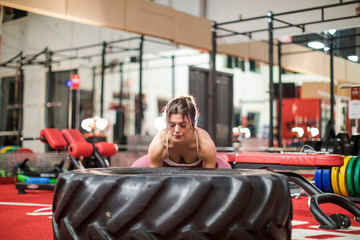 Young attractive woman lifting up a tractor tire