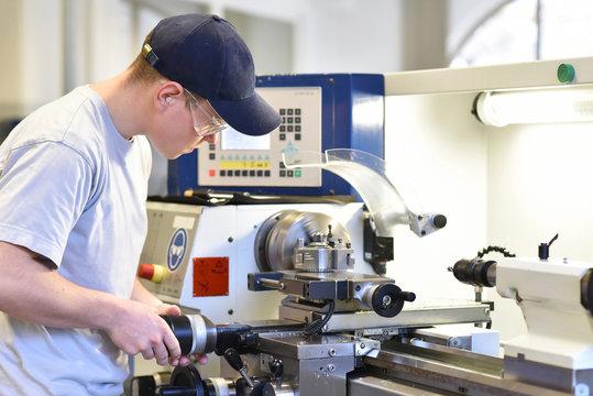 technsiche Berufsausbildung - junger auszubildender an der Drehbank einer C_NC Maschine // young apprentice in vocational training working on a turning machine in the industry