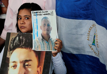 A girl holds a picture during a news conference in Managua