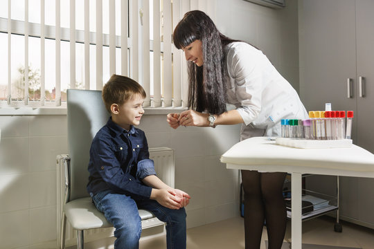 A medical worker opens a bactericidal band-aid for a smiling boy