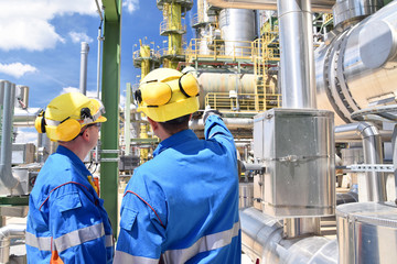 chemical industry plant - workers in work clothes in a refinery with pipes and machinery