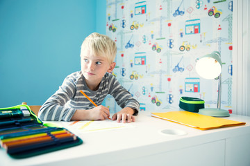 Boy doing homework at desk in children's room