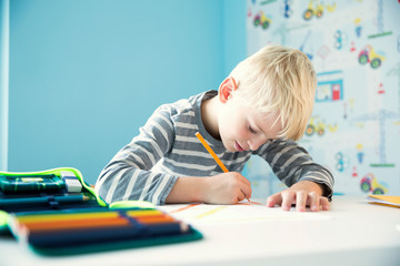 Focused boy doing homework at desk in children's room