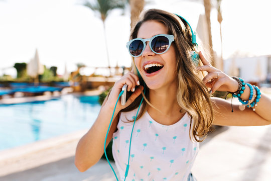 Close-up portrait of excited curly tanned girl in trendy sunglasses walking by swimming pool outside. Funny cheerful young woman in headphones enjoying music, while resting outdoor on summer resort.