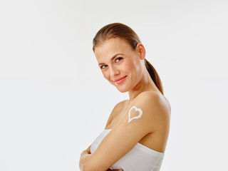 Young woman applying body creme, heart on shoulder