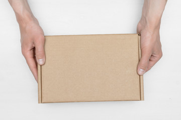 A parcel cardboard box in a delivery man hands on a white wooden table background. Delivery service concept.