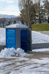 Portapotty in snow at a park