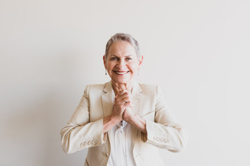 Waist up view of senior woman in cream jacket with hands clasped togther - consensus concept (selective focus)
