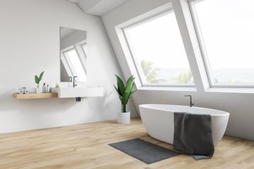 Attic white bathroom corner, tub and sink