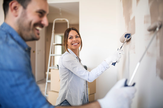 Beautiful woman painting wall with roller.