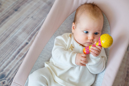Adorable baby girl having fun in bouncer. Toddler playing with colorful rattle toy. Activities for infants