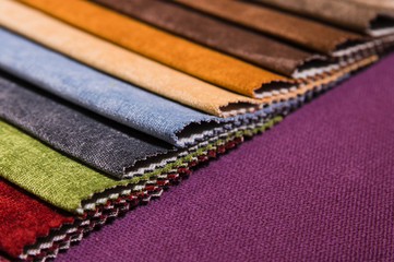 Colorful and bright fabric samples of furniture and clothing upholstery. Close-up of a palette of...