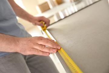 Man measuring kitchen furniture indoors, closeup. Construction tool