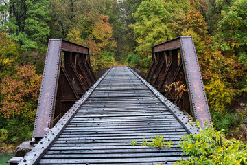 Old riveted steel train trestle bridge disappears into the lush autumn colored forest of Arkansas. This rustic old railroad crossing seems to have been forgotten by time itself