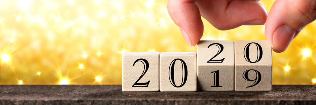 Hand Changing Date From 2019 To 2020 On Wooden Cube Calendar With Gold Glittering Background And Yellow Sparkles / New Year`s Concept