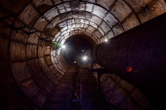 Round concrete underground tunnel of heating duct system with rusty pipes