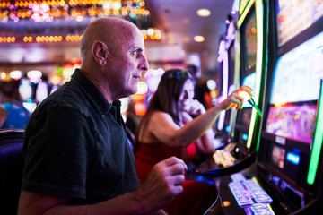elderly tourist playing slot machines and gambling in casino