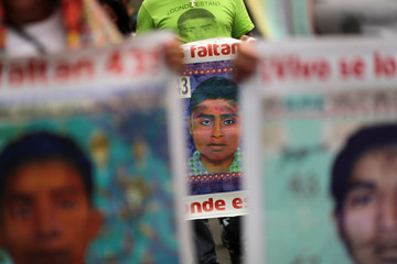 Relatives hold pictures of missing students of Ayotzinapa College Raul Isidro Burgos during a march in Mexico City