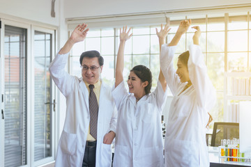 Scientists hands rais up,Group of diversity people teamwork in laboratory,Success and reserch working