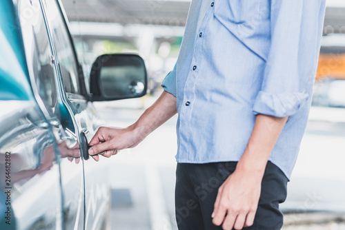 a man locking up or unlocking car door with key in hand