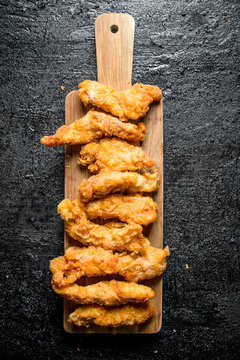 Chicken strips on a wooden cutting Board.
