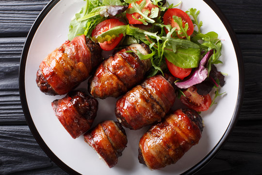 Smoked Armadillo eggs with jalapeno and cheese wrapped in bacon served with fresh salad close-up on a plate. horizontal top view