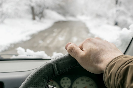 Man's hand on the steering wheel of a car that moves in the snowy forest on a wet slushy road