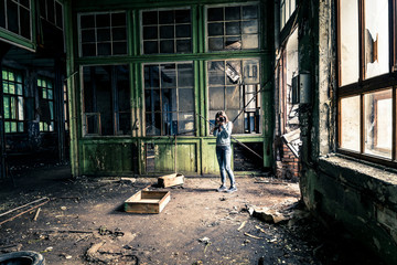 Young girl in old, ruined factory is taking a picture.