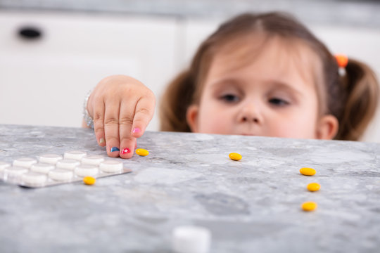 Girl Taking Tablets From Worktop