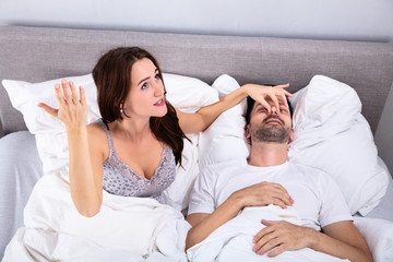Woman Holding Her Husband's Nose To Stop Him From Snoring