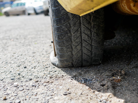 Flat tire on  parking car, shallow depth of field, copy space.