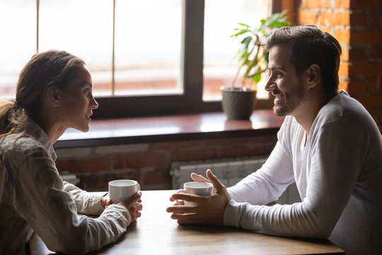 Couple sitting in cafe talking drinking tea or coffee