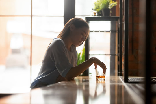 Young sad woman sitting on bar counter drinking alcohol drinks