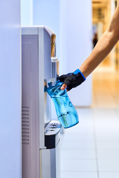 A young woman collects water from the cooler in bottle to quench her thirst after long intense workout. Close-up of hand in sports glove holding blue transparent bottle