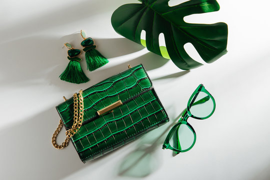Feminine accessories collage with handbag, sunglasses and tropical leaf. Flat lay, top view. Summer fashion concept