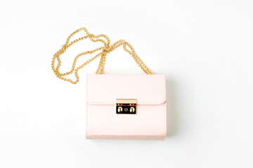 Wall Mural - Fashion pale pink handbag on white  background. Flat lay, top view. Spring/summer fashion concept in pastel colored