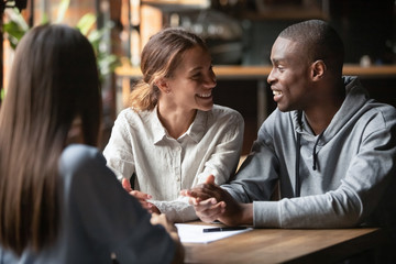 Diverse happy couple sitting at table with real estate agent