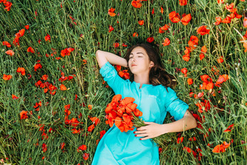 Young woman lying on summer poppy flowers meadow.