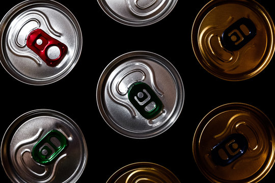 Metal beer cans background in the dark. Top view of various aluminum beverage cans.