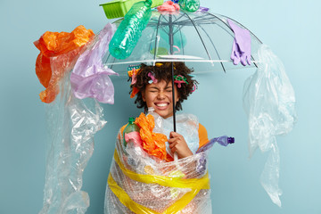 Emotional dark skinned woman stands under plastic umbrella, smirks face and shows white teeth, demonstrates environment awareness, wrapped in polyethylene film, isolated on blue. Zero waste concept