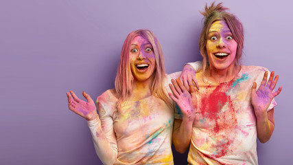 Candid shot of cheerful two women raise hands, show palms, surprised and glad to celebrate Holi festival in India, stand together over purple background, free space for your promotion. Day of colors Fotoväggar