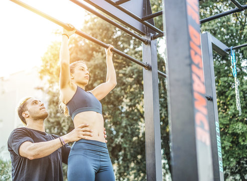 Personal trainer helping his friend to do pull up during the calisthenics session - Couple doing sport together in the park at sunset