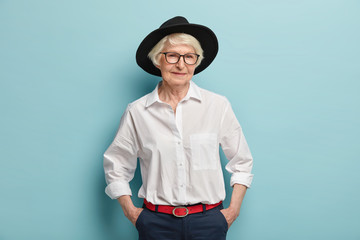 Fashionable mature woman wears stylish black hat, white shirt and trousers with red belt, keeps hands in pockets, has glad expression, isolated over blue background. People, age and fashion concept