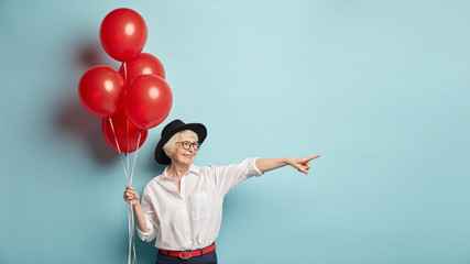 Glad female pensioner advertises something on distance, points fore finger aside, has cheerful expression, wears stylish clothes, holds red air balloons, isolated over blue wall. Old woman has holiday