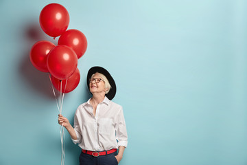 Indoor shot of pleasant looking cheerful woman of old age holds helium air balloons, comes on party for elderly people to congratulate her best friend, focused above, wears fashionable clothes