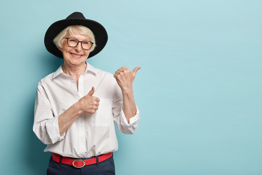 Image of attractive wrinkled woman with appealing look, feels refreshed, young for her age, points at upper right corner, satisfied with product, wears white shirt, black headgear, optical glasses