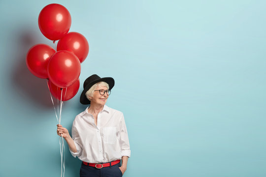 Delighted smiling lady has wrinkled skin, has party at work with colleagues, celebrates retirement, holds red air balloons, wears fashionable clothes, isolated over blue studio wall with blank space