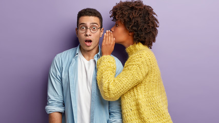 Photo of Afro American woman whispers secret to boyfriend, tells shocking news. Astonished young man keeps jaw dropped from surprisement, hears terrible rumors, isolated over purple background Wall mural