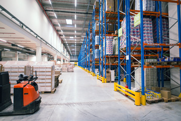 Warehouse storage facility interior. Large distribution center with shelves full of palette boxes and forklift machine. Wall mural